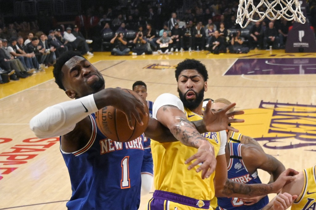 New York Knicks forward Bobby Portis, left, and Los Angeles Lakers forward Anthony Davis reach for a rebound during the first half of an NBA basketbal...