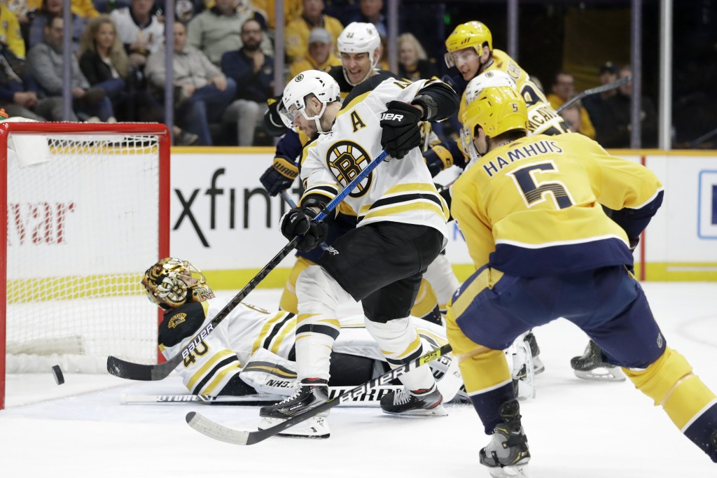 Boston Bruins center David Krejci, of the Czech Republic, clears the puck as goaltender Tuukka Rask (40), of Finland, falls on his back in the second ...