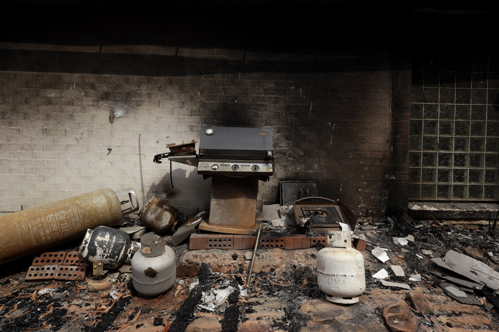 A barbeque and gas bottles are strewn on around of the destroyed home of Justin Kam and Helena Wong at Balmoral, Australia, Tuesday, Jan. 7, 2020. Kam...