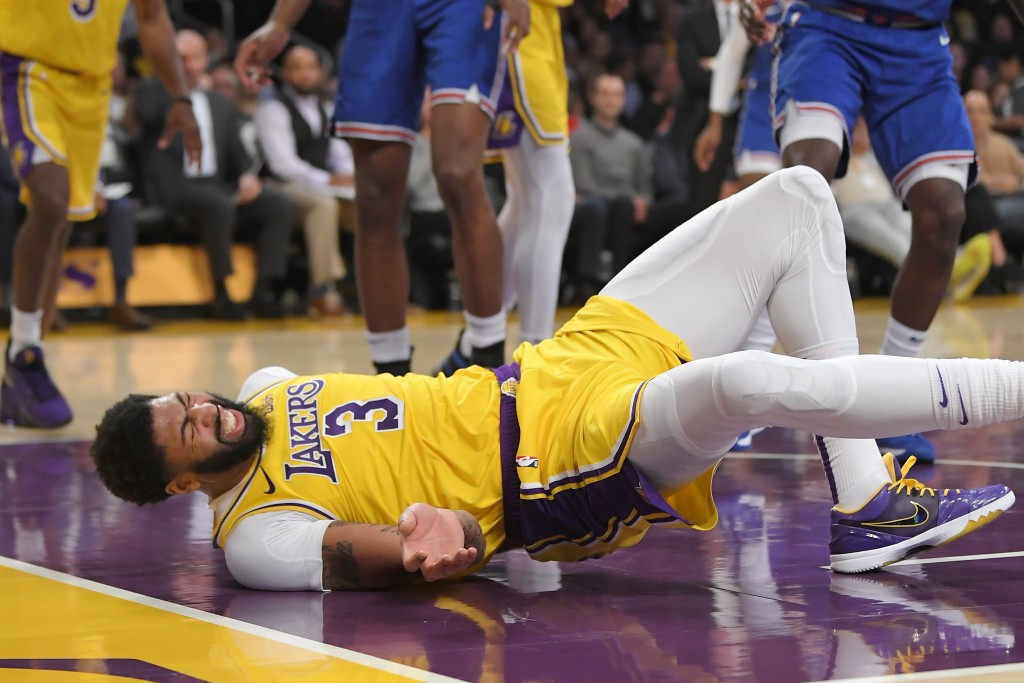 Los Angeles Lakers forward Anthony Davis winces as he hits the court after falling while trying to defend against a shot by New York Knicks forward Ju...