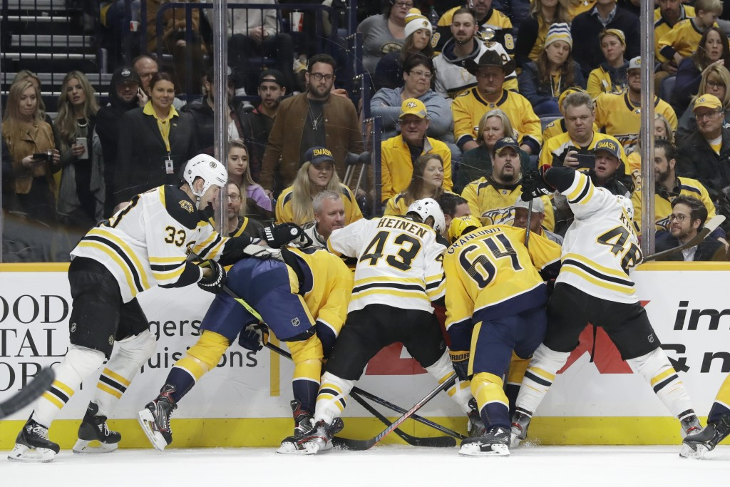 A group of Boston Bruins and Nashville Predators battle for the puck trapped against the boards in the second period of an NHL hockey game Tuesday, Ja...