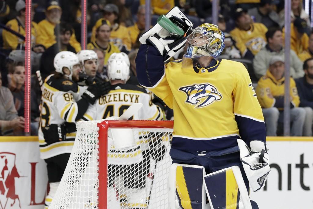 Nashville Predators goaltender Pekka Rinne (35), of Finland, takes a drink as Boston Bruins players celebrate a goal by right wing David Pastrnak (88)...
