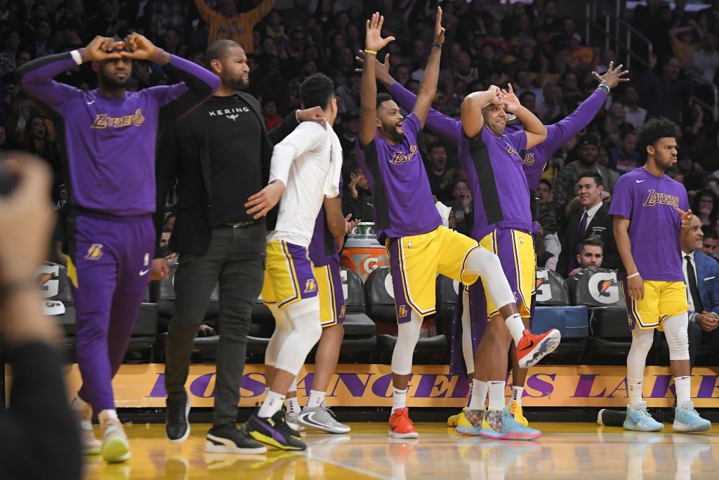 Los Angeles Lakers celebrate from the bench after guard Alex Caruso scored during the first half of the team's NBA basketball game against the New Yor...