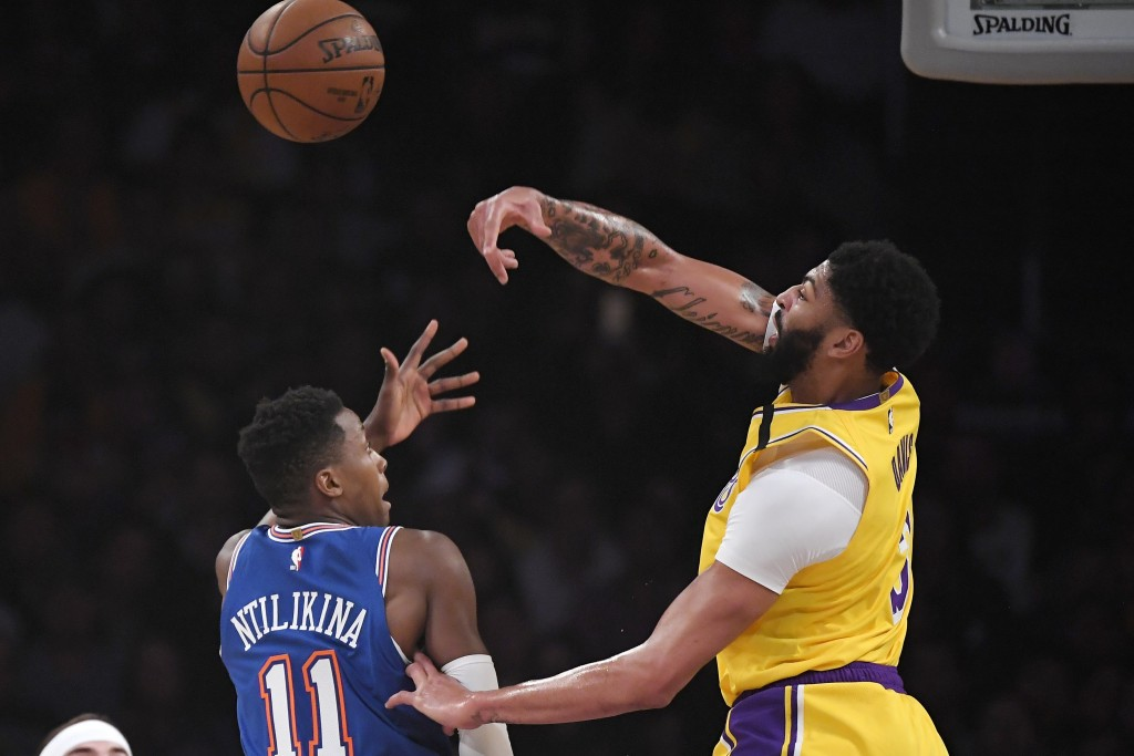 Los Angeles Lakers forward Anthony Davis, right, rejects a shot by New York Knicks guard Frank Ntilikina during the first half of an NBA basketball ga...