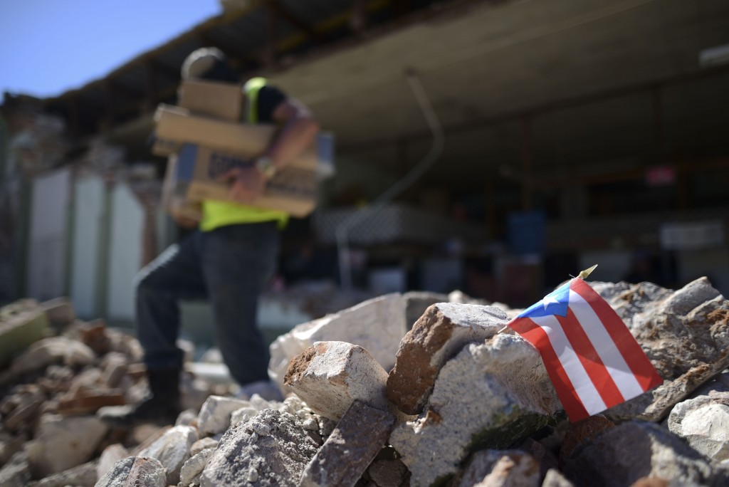 A Puerto Rican flag hangs within the rubble, after it was placed there where store owners and family help remove supplies from Ely Mer Mar hardware st...