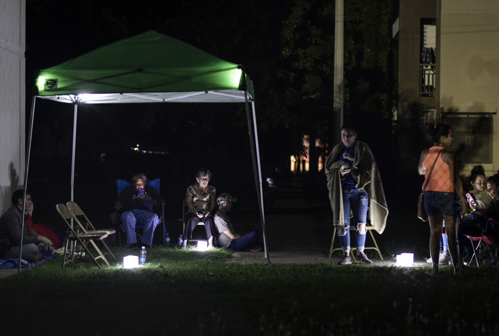 Neighbors remain outdoors using camping tents and portable lights for fear of possible aftershocks on their first night after a 6.4-magnitude earthqua...
