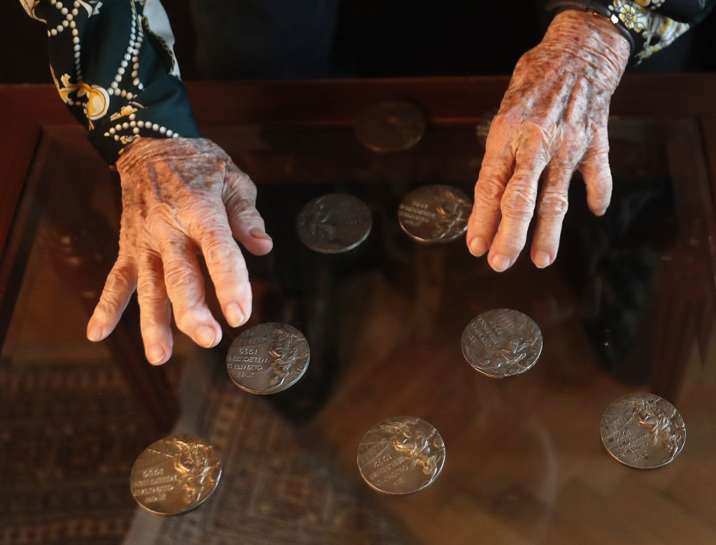 Agnes Keleti, former Olympic gold medal winning gymnast, touches her medals in Budapest, Hungary Wednesday Jan. 8, 2020. Although she turned 99 on Thu...