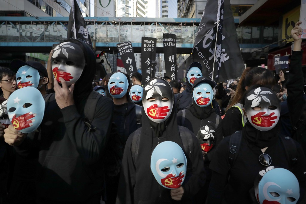 FILE - In this Dec. 8, 2019, file photo, pro-democracy protesters wear masks depicting the hand with Chinese Communist party emblem covering their mou...