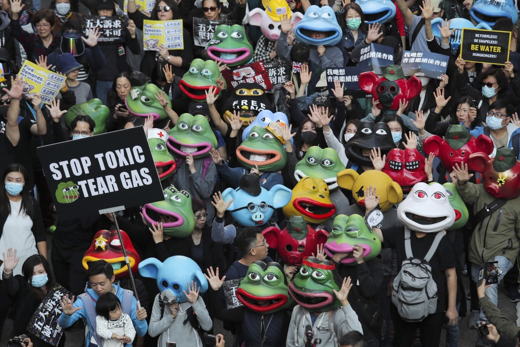 FILE - In this Dec. 8, 2019, file photo, pro-democracy protesters wear masks including those for Pepe the frog during a march in Hong Kong. Trump sign...