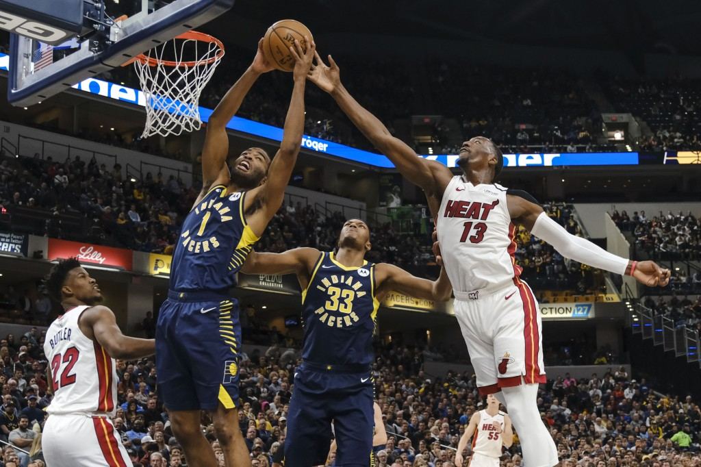 Indiana Pacers forward T.J. Warren (1) pulls down a rebound in front of Miami Heat center Bam Adebayo (13) during the first half of an NBA basketball ...