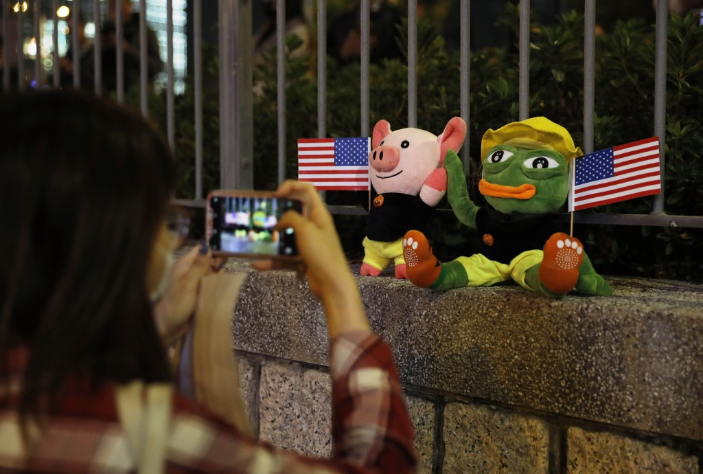 FILE - In this Nov. 28, 2019, file photo, a woman takes a photograph of plush toys of Pepe the Frog and LIHKG Pig, two symbols which have been used by...