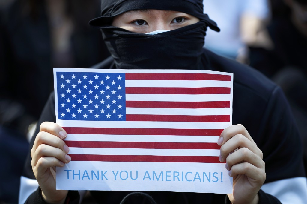 FILE - In this Dec. 1, 2019, file photo, a protester holds a placard showing the American flag during a rally in Hong Kong. Trump signs, Pepe the Frog...