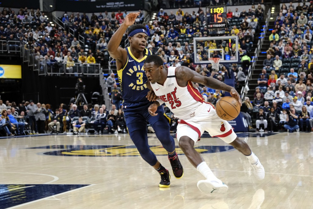 Miami Heat guard Kendrick Nunn (25) drives around Indiana Pacers guard Aaron Holiday (3) during the first half of an NBA basketball game in Indianapol...