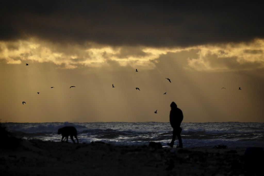 A person walks with a dog  on the beach as heavy clouds gather over the Mediterranean Sea and the Alexander River, in Hefer Valley, Israel, Thursday, ...