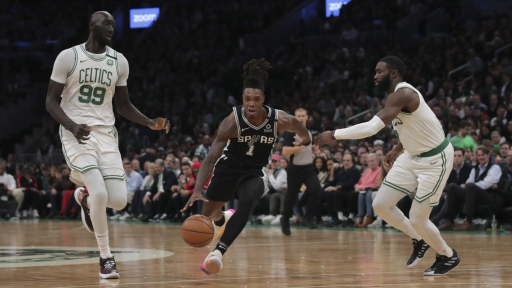 San Antonio Spurs guard Lonnie Walker IV (1) drives between Boston Celtics center Tacko Fall (99) and guard Jaylen Brown (7) during the first half of ...