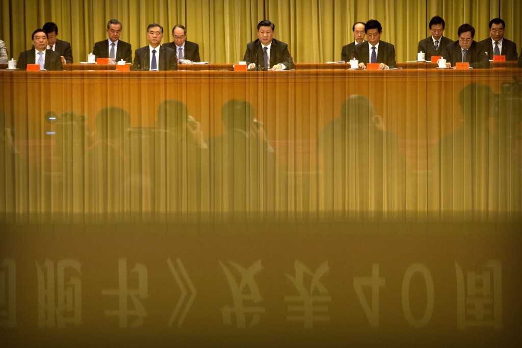 FILE - In this Jan. 2, 2019, file photo, a banner is reflected in a polished surface as Chinese President Xi Jinping, center, speaks during an event t...