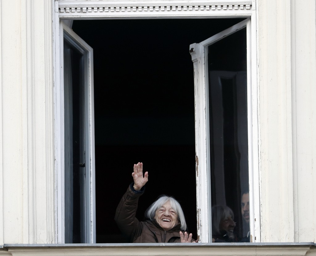 Agnes Keleti, former Olympic gold medal winning gymnast, waves from a window of her apartment in Budapest, Hungary Wednesday Jan. 8, 2020. Keleti is t...