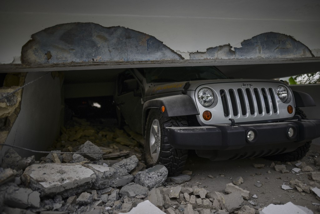 A car is crushed under a home that collapsed after the previous day's magnitude 6.4 earthquake in Yauco, Puerto Rico, Wednesday, Jan. 8, 2020. More th...