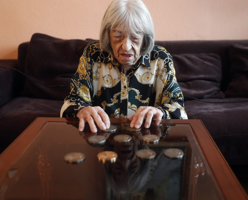 Agnes Keleti, former Olympic gold medal winning gymnast, looks at her medals at her apartment in Budapest, Hungary Wednesday Jan. 8, 2020. Keleti is t...