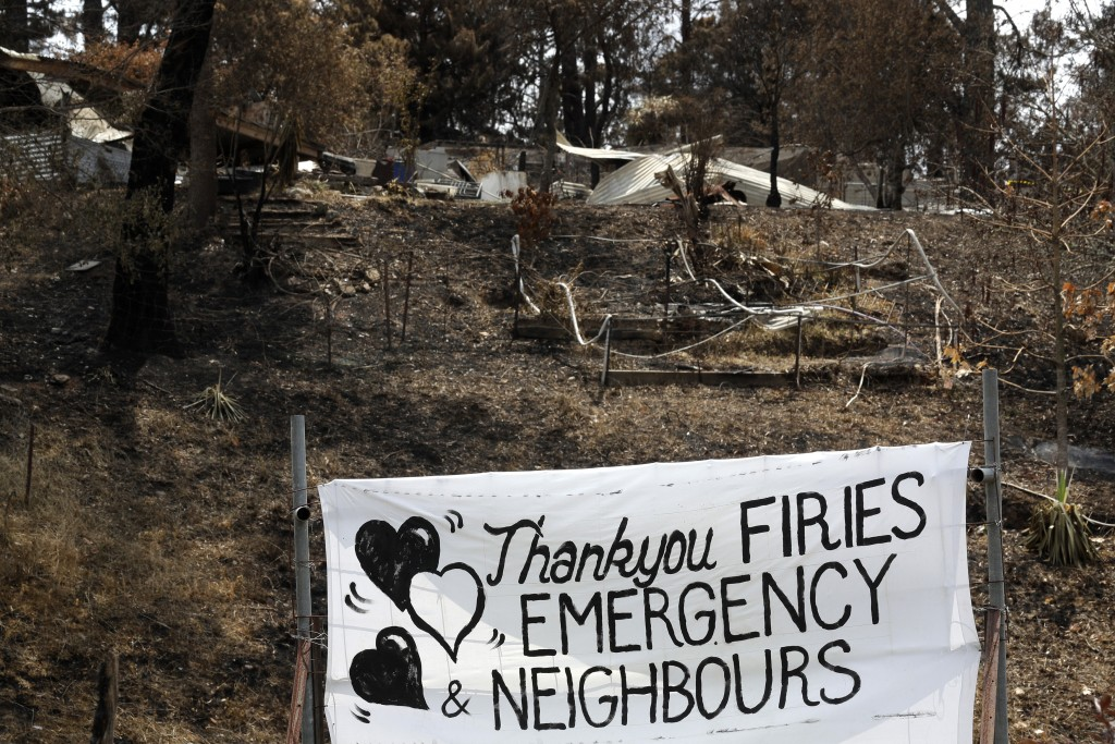 "A sign is displayed beside a burned out house near Mogo, Australia, Thursday, Jan. 9, 2020, thanking ""firies"" a colloquial term for firefighters. Hous..."