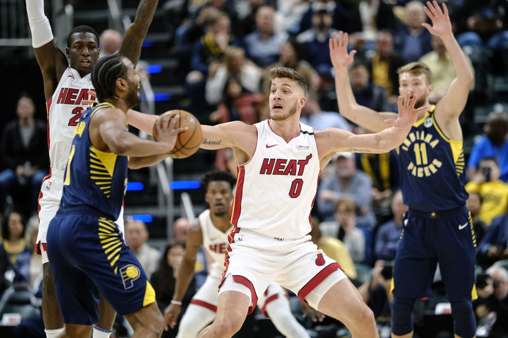 Miami Heat forward Meyers Leonard (0) defends Indiana Pacers forward T.J. Warren (1) during the first half of an NBA basketball game in Indianapolis, ...