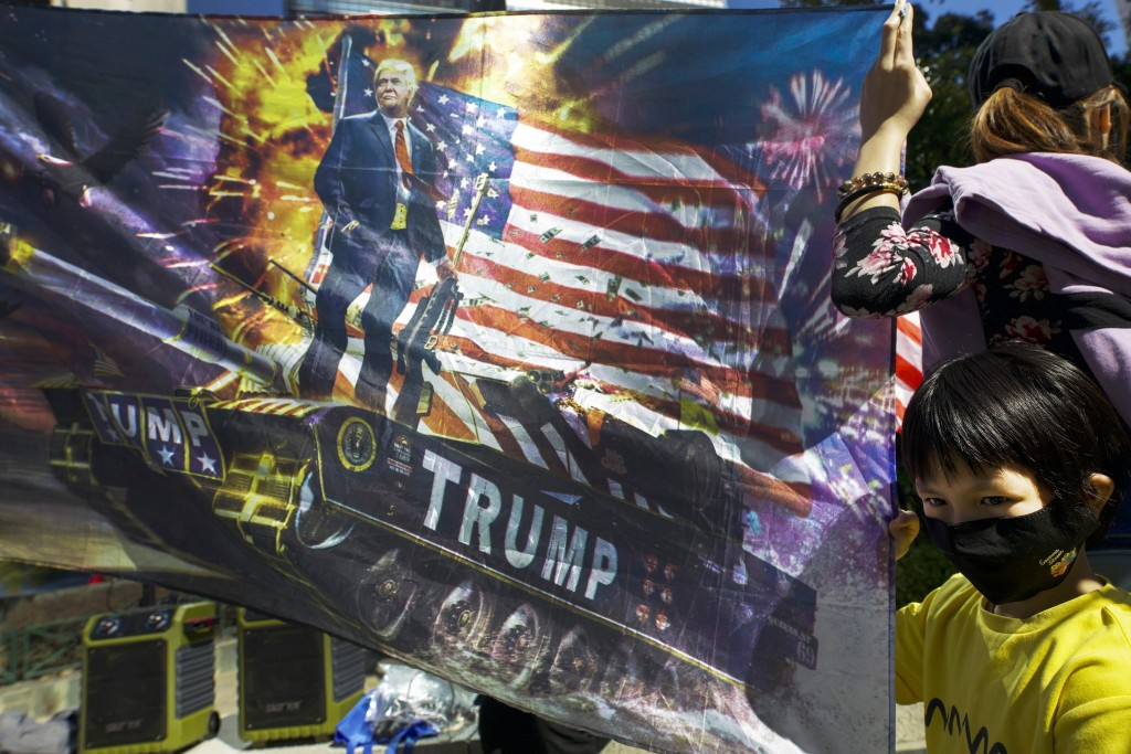 FILE - In this Dec. 1, 2019, file photo, a masked child holds a flag depicting U.S. President Donald Trump holding a rifle on a tank during a rally in...
