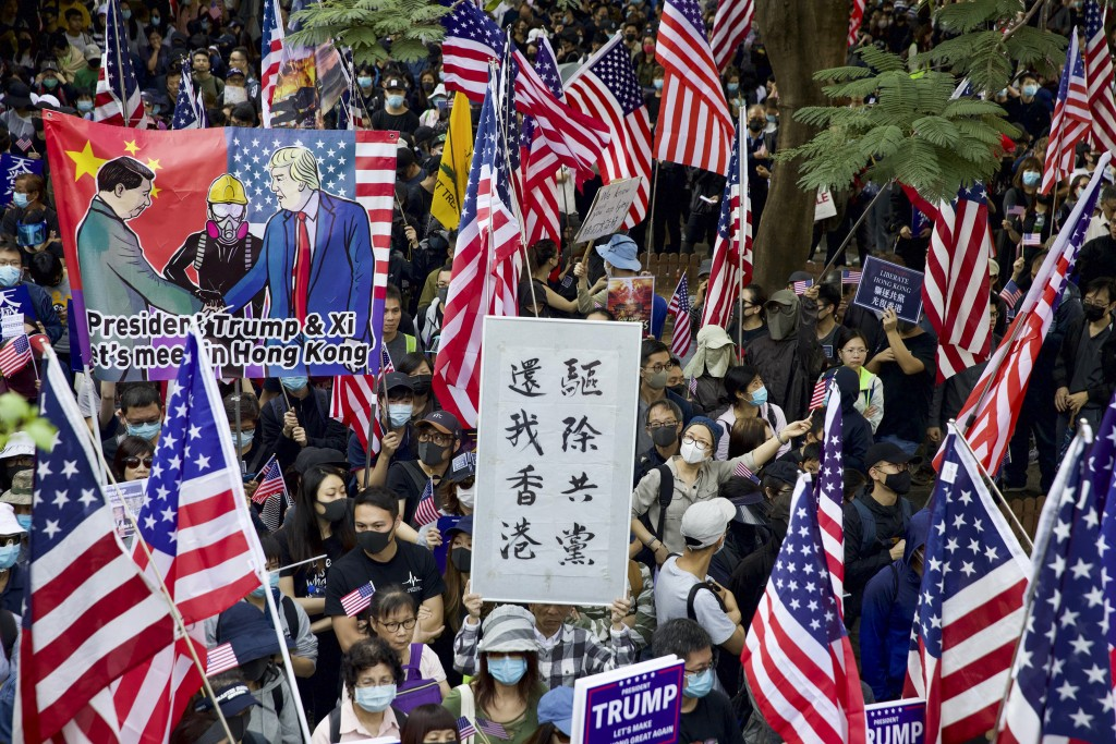 """FILE - In this Dec. 1, 2019, file photo, protesters wave United States flags and a banner with the words """"Chase away Communists and return my Hong Kon..."""
