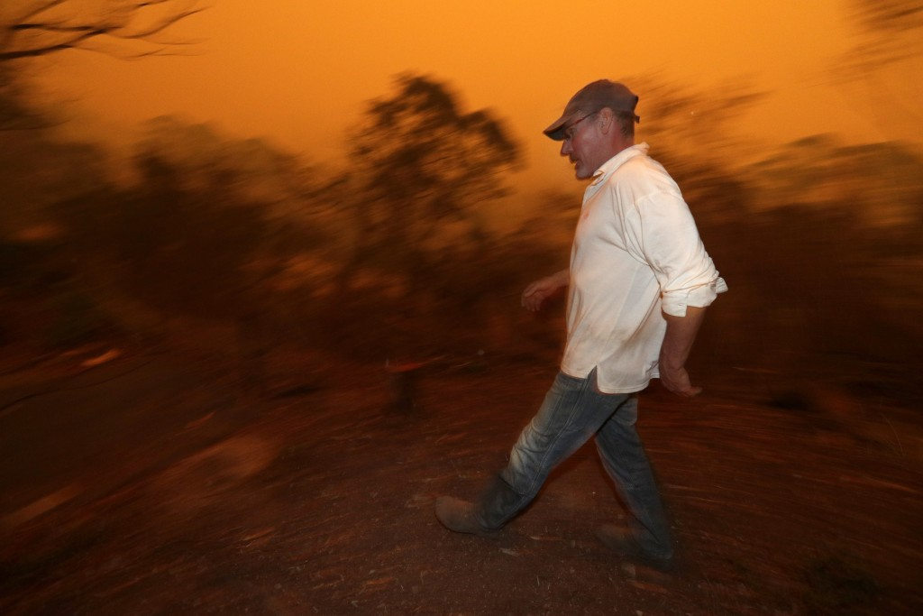 Evan Harris rushes around his property preparing to minimize fire impact at Burragate, Australia, Friday, Jan. 10, 2020, as a nearby fire threatens th...