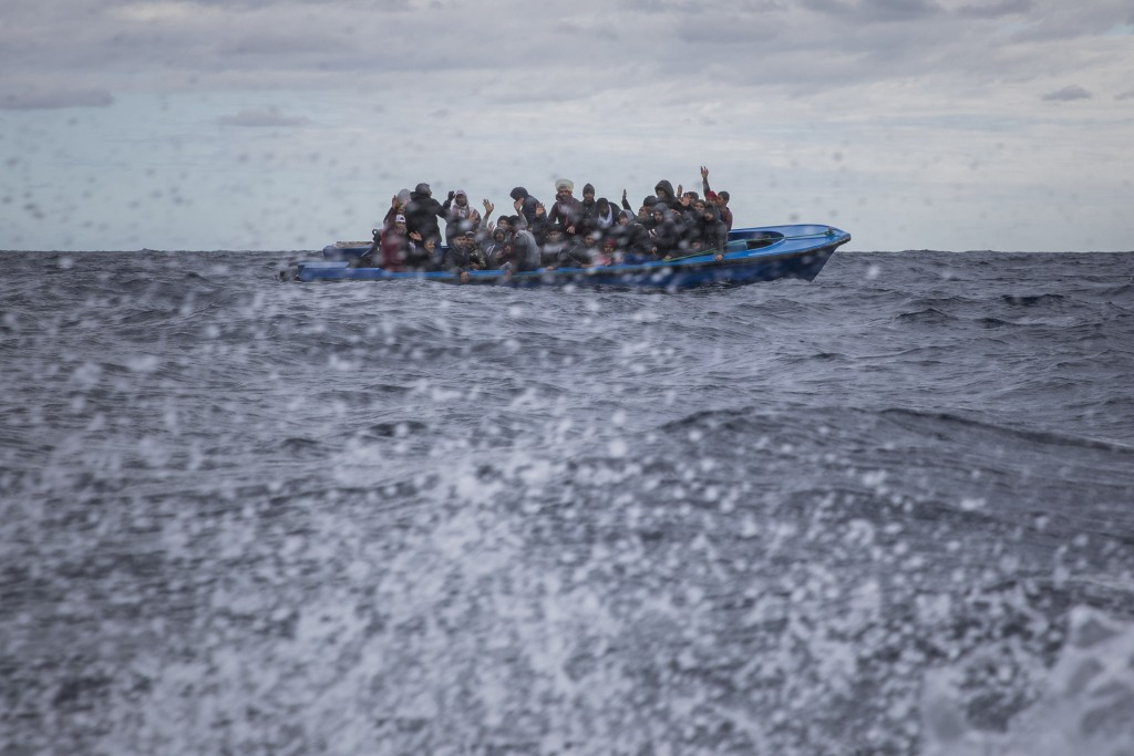 Men from Morocco and Bangladesh react on an overcrowded wooden boat, as aid workers of the Spanish NGO Open Arms approach them in the Mediterranean Se...