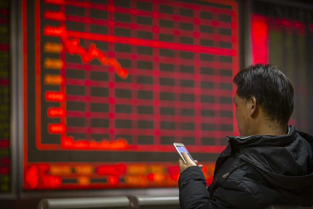 A Chinese investor uses his smartphone as he monitors stock prices at a brokerage house in Beijing, Friday, Jan. 10, 2020. Asian shares rose Friday as...