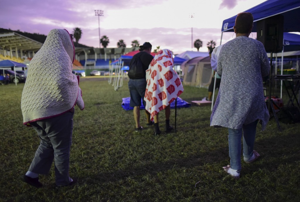 People get up after spending the night in a baseball stadium amid aftershocks and without electricity after the 6.4 magnitude earthquake in Guayanilla...