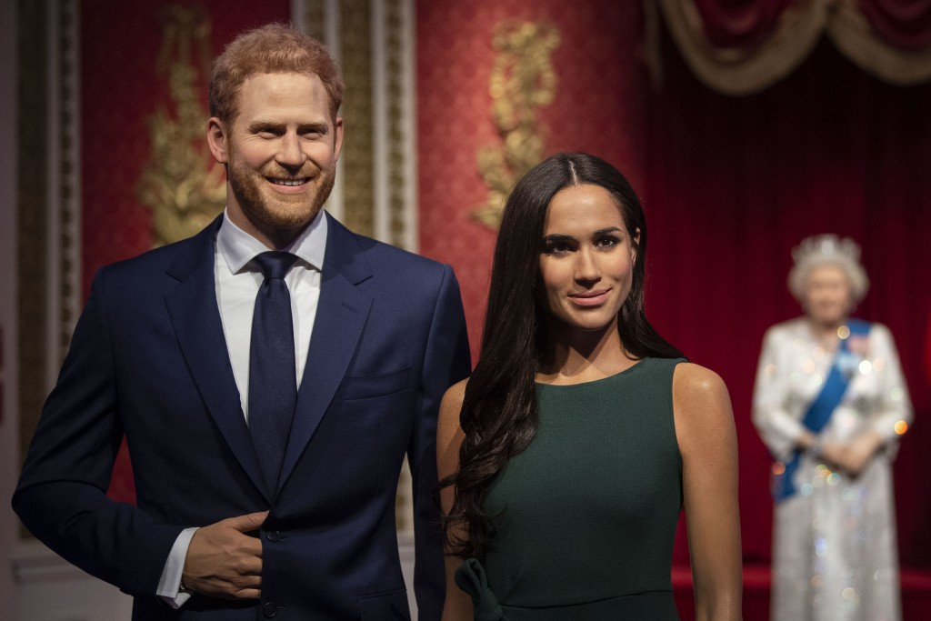 The figures of Britain's Prince Harry and Meghan, Duchess of Sussex, left, are moved from their original positions next to Queen Elizabeth II, Prince ...