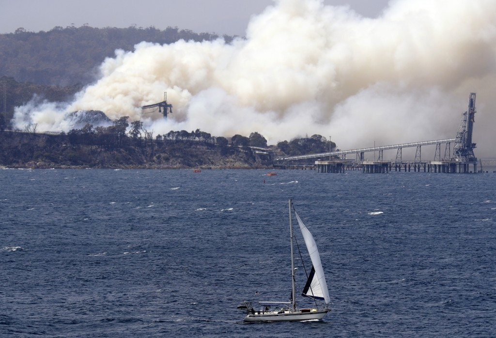 A yacht sails past a burning woodchip mill as the wildfires hits the town of Eden, New South Wales, Australia, Friday, Jan. 10, 2020. The wildfires ha...