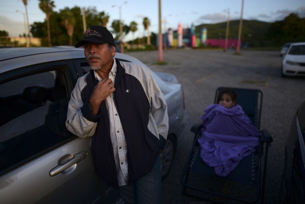 Eddie Correa, 61, and his 10-year old grand daughter Delancy Torres are up early after spending the night in their car at a parking lot after Tuesday'...