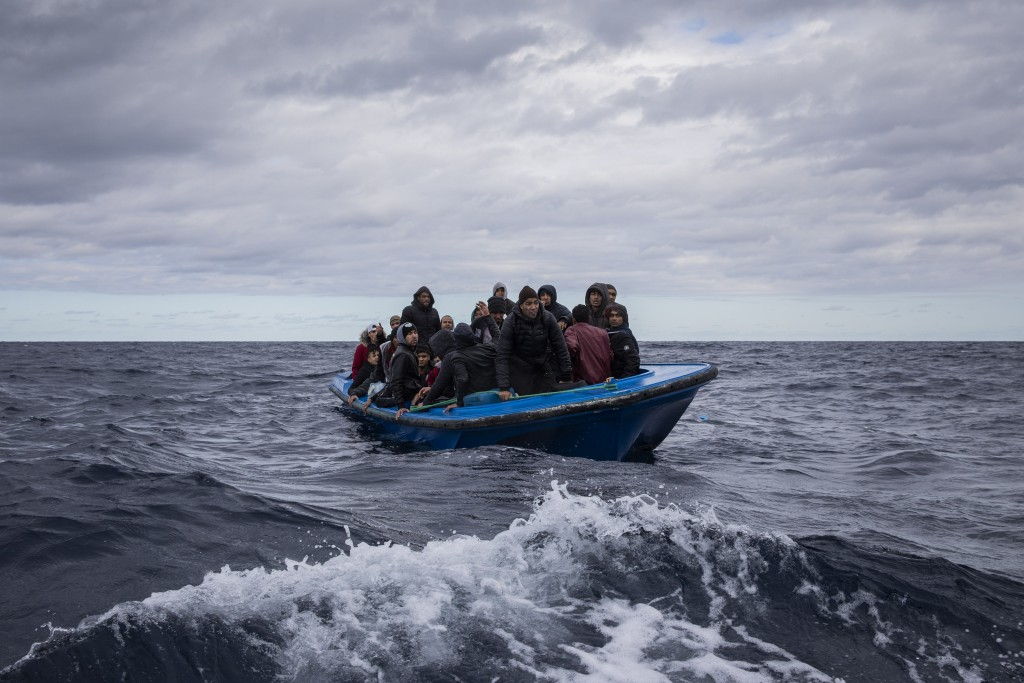 Men from Morocco and Bangladesh look out from an overcrowded wooden boat, as aid workers of the Spanish NGO Open Arms approach them in the Mediterrane...