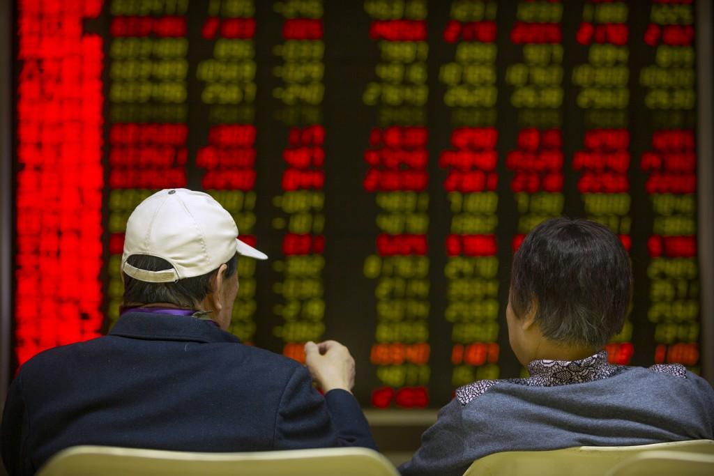 Chinese investors monitor stock prices at a brokerage house in Beijing, Friday, Jan. 10, 2020. Asian shares rose Friday as worries receded the United ...