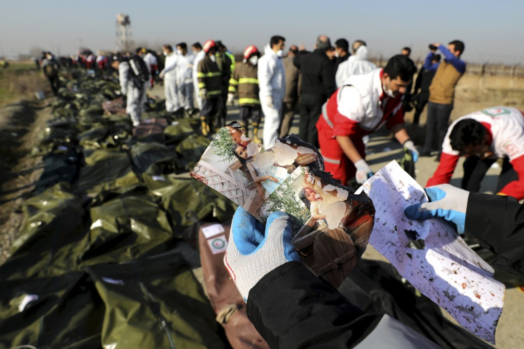 FILE - In this Wednesday, Jan. 8, 2020 file photo, a rescue worker shows pictures of a girl recovered from a Ukrainian plane crash site in Shahedshahr...