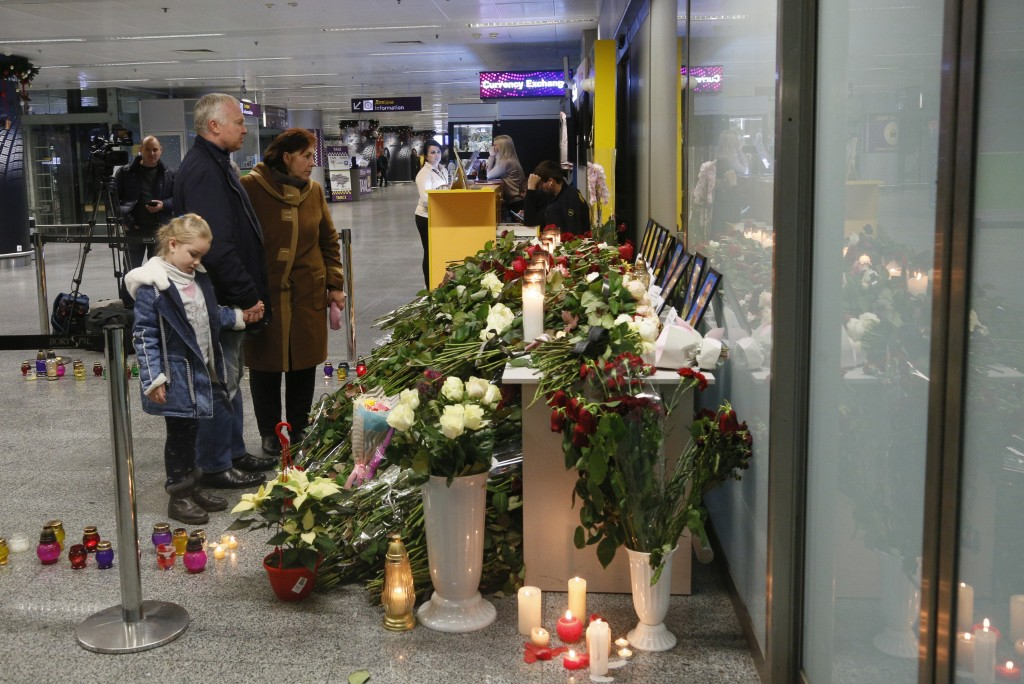 FILE - In this Thursday, Jan. 9, 2020 file photo, people look at tributes and flowers at Borispil international airport outside in Kyiv, Ukraine, for ...