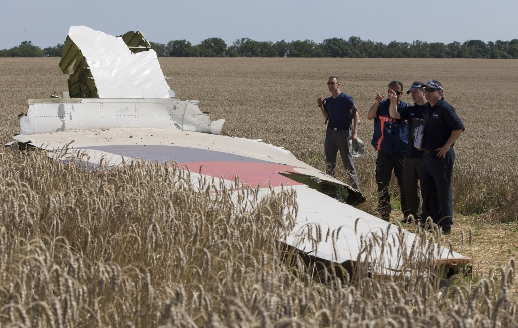 FILE - In this Friday, Aug. 1, 2014 file photo, Australian and Dutch investigators examine a piece of the Malaysia Airlines Flight 17 plane, near the ...