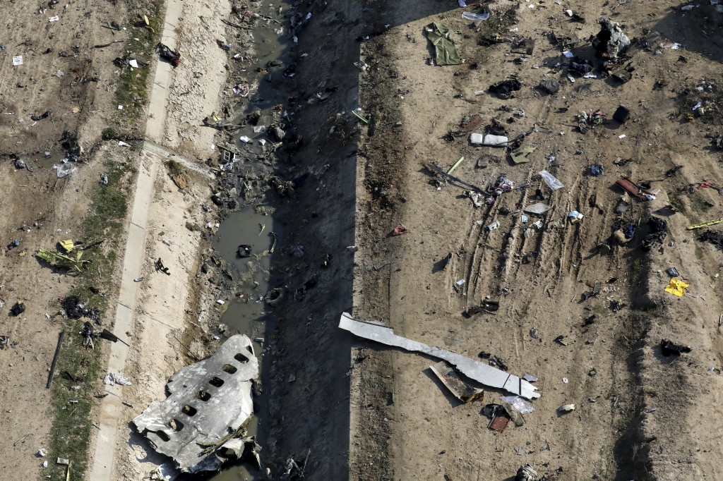 In this Wednesday, Jan. 8, 2020 photo, wreckage from a Ukrainian plane  is seen on the ground and inside a water canal in Shahedshahr, southwest of th...