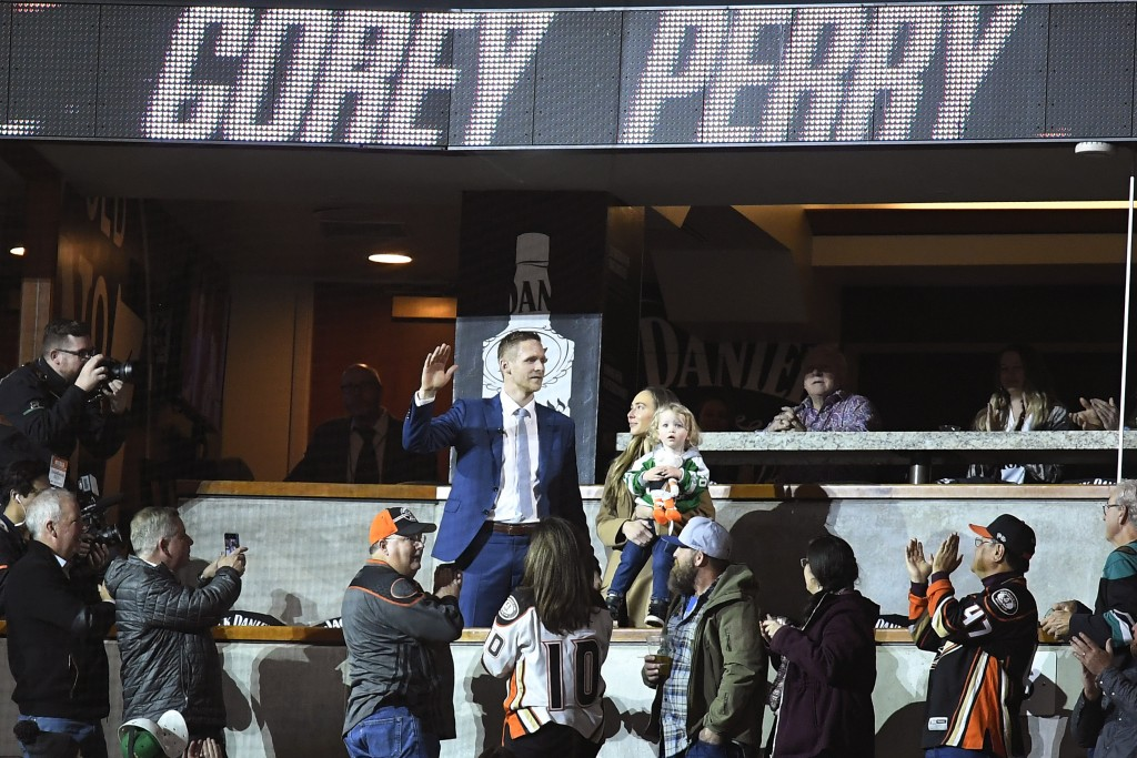 Dallas Stars right wing Corey Perry waves to fans as he is acknowledged in a video presentation during a timeout in the first period of the team's NHL...