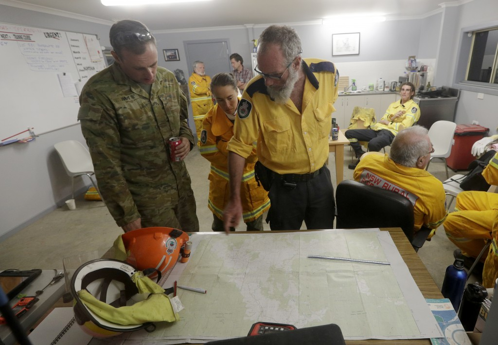 Firefighters and members of the army discuss a nearby fire threat at the Burragate, Australia, firehouse, Friday, Jan. 10, 2020. Thousands of people a...