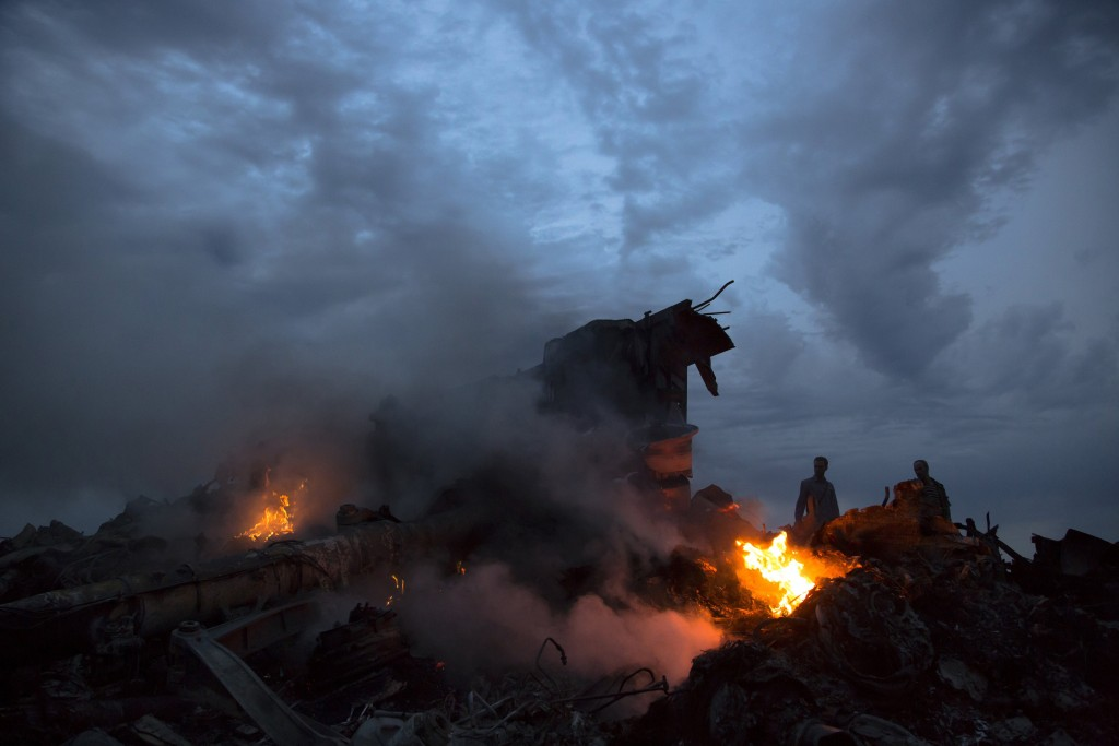 FILE - This July 17, 2014 file photo shows people walking amongst burning debris at the crash site of Malaysia Airlines Flight 17 near the village of ...