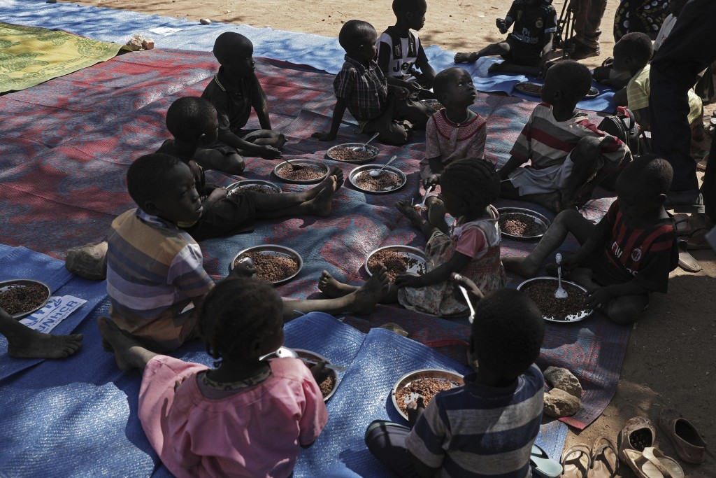 Children eat food distributed during a visit organized by The World Food Program (WFP) at Koge school, in the conflict-affected remote town of Kauda, ...