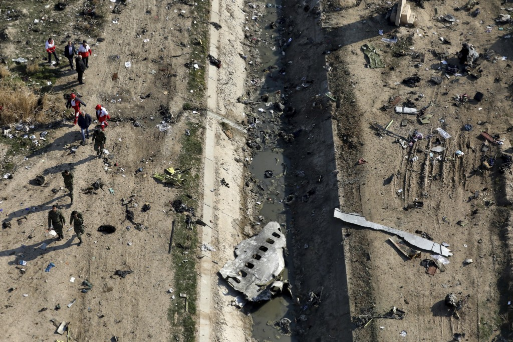 FILE - In this Wednesday, Jan. 8, 2020 file photo, rescue workers search the scene where a Ukrainian plane crashed in Shahedshahr, southwest of the ca...