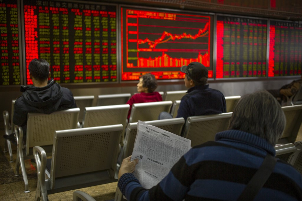 A Chinese investor reads a newspaper as she monitors stock prices at a brokerage house in Beijing, Friday, Jan. 10, 2020. Asian shares rose Friday as ...