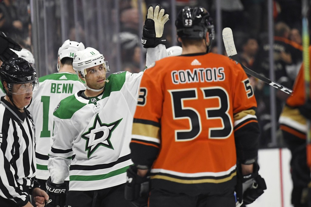 Dallas Stars center Andrew Cogliano, left, waves to fans as he is acknowledged in a video presentation, as Anaheim Ducks left wing Max Comtois skates ...