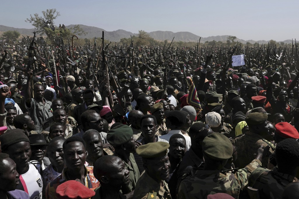 People chant slogans in support of a secular state during a visit organized by The World Food Program (WFP) in the conflict-affected remote town of Ka...
