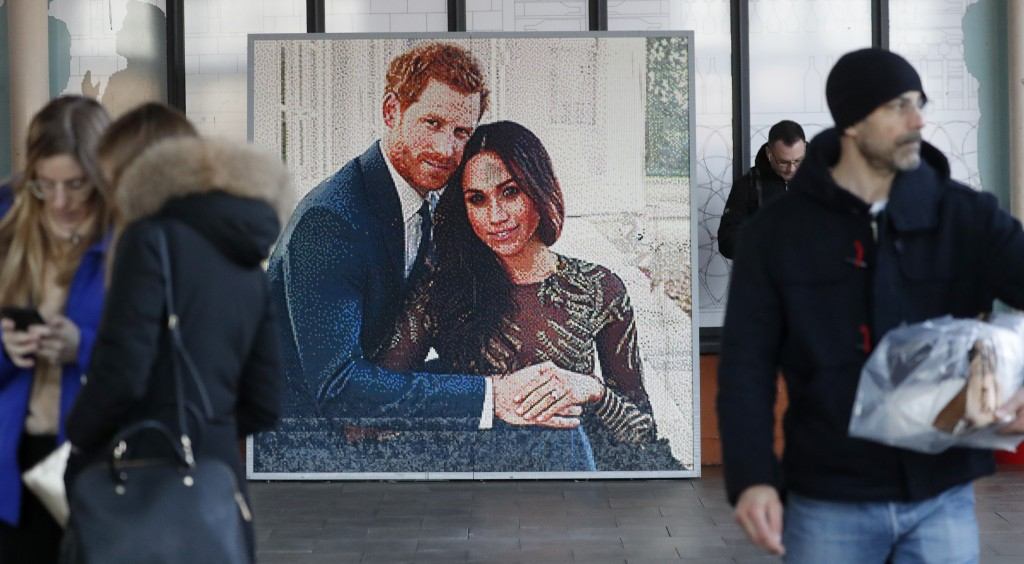 People walk past a picture of Britain's Prince Harry and Meghan Duchess of Sussex, in Windsor, Friday, Jan. 10, 2020. Britain's Prince Harry and his w...