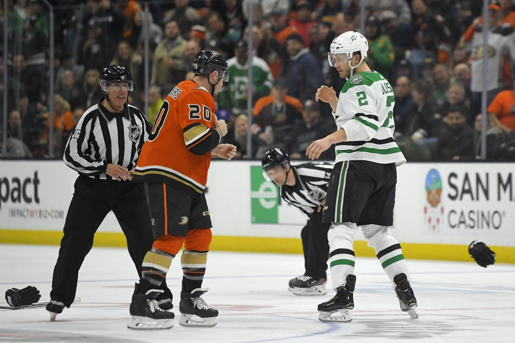 Anaheim Ducks left wing Nicolas Deslauriers, left, and Dallas Stars defenseman Jamie Oleksiak, right, get set to fight as linesmen watch during the se...